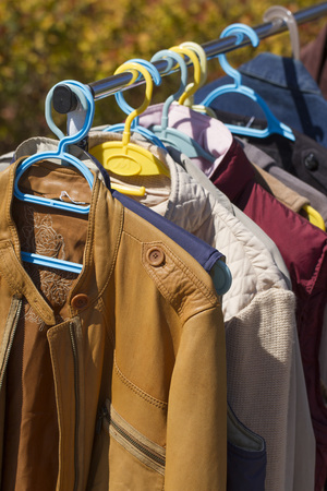 reusing: clothes and leather jacket displayed at garage sale Stock Photo