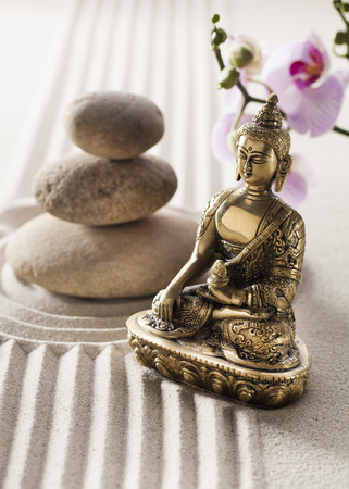 hedonism: bronze beautiful Buddha in sand curves and smooth pebbles