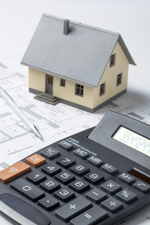housing market and investment concept with miniature house with drawing tools on computer rendering Фото со стока