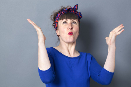 fifties: success concept - extrovert 30s woman with fifties hairstyle expressing fun,looking up to enjoy winning competition,studio shot