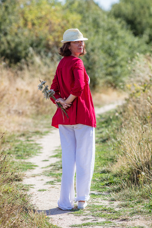wandering: countryside walk - smiling lady with summer hat wandering alone with picked field flowers in her back,rear view,summer daylight Stock Photo