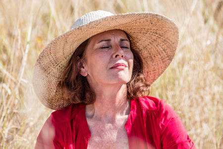 warmth: outdoors relaxation - happy beautiful lady closing eyes in dry summer field to enjoy warmth with sun protection,summer daylight Stock Photo