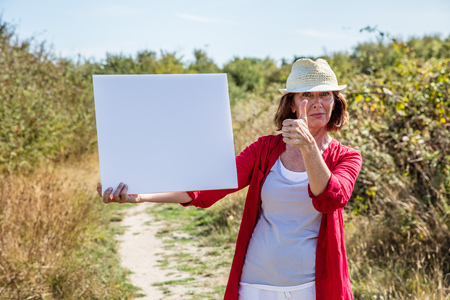 50s: nature teasing - smiling 50s woman with summer hat agreeing to message on white blank panel,walking on countryside path Stock Photo