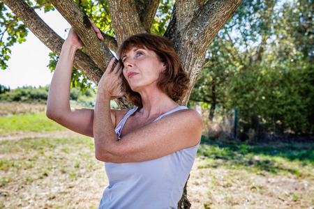 50's: middle aged wellness - thinking 50s woman under a tree for metaphor of nostalgia and imagination,summer daylight Stock Photo