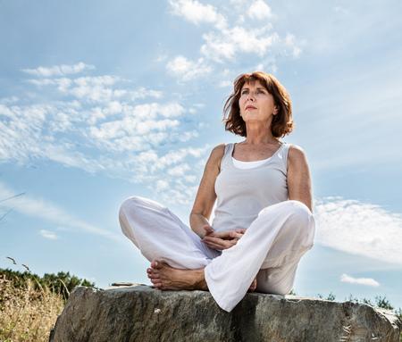 mature people: breathing outdoors - beautiful middle aged woman sitting on a stone in yoga lotus position, wearing white, seeking for balance over summer blue sky,low angle view Stock Photo
