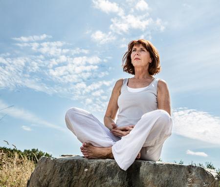 mujer sentada: respirar aire libre - hermosa mujer de mediana edad sentado en una piedra en posici�n de loto de yoga, vistiendo de blanco, buscando el equilibrio sobre el cielo de verano azul, �ngulo de visi�n baja Foto de archivo