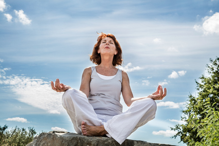 inner beauty: exercising outdoors - beautiful middle aged woman sitting on a stone in yoga lotus position, wearing white, seeking for serenity over blue sky,low angle view