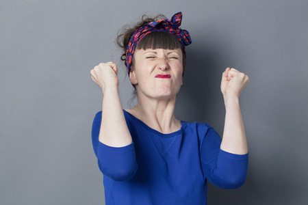 exasperation: success concept - tensed 30s woman with fifties hairstyle frowning to fight, expressing motivation or disappointed regret,studio shot Stock Photo