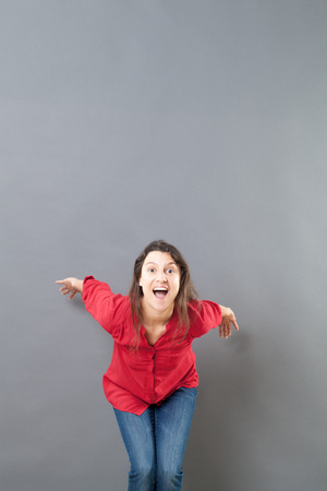 euphoria: success concept - excited 30s woman ready to jump to express euphoria or vitality,studio shot Stock Photo