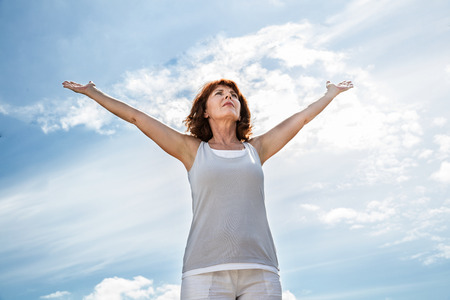 opening up: breathing outside - older yoga woman opening up her arms to exercise,practicing meditation for freedom over summer blue sky,low angle view