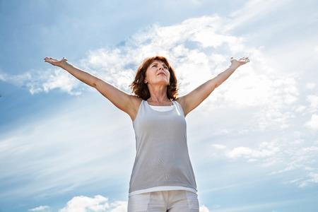 persona respirando: respirar fuera - Yoga de la mujer más vieja abriendo sus brazos para hacer ejercicio, practicar la meditación de la libertad sobre el cielo azul del verano, ángulo de visión baja Foto de archivo