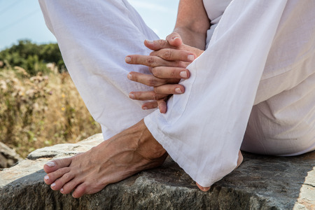 inner peace: spirituality outdoors - closeup of praying hands and bare feet of a yoga woman sitting on a stone in lotus position, wearing white,low angle view