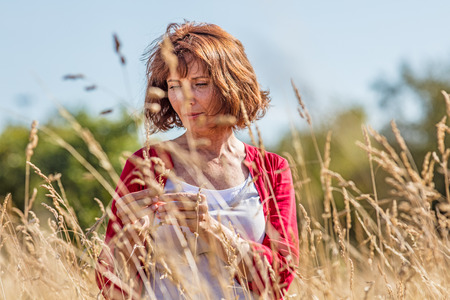 wandering: outdoors relaxation - gorgeous middle aged woman enjoying quietness,wandering in dry high meadows, summer daylight