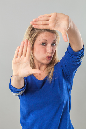 picture framing: picture framing concept - pouting young blond woman making a frame with her hands for photographer, studio shot