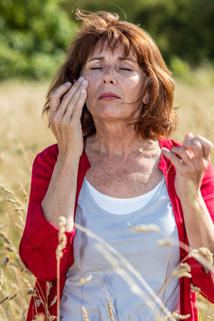 50s: outdoors illness - beautiful 50s woman with freckles suffering from headache, rhinitis or hay fever,summer daylight Stock Photo