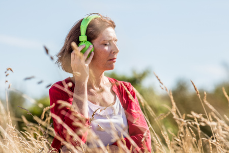 quietness: outdoors relaxation - gorgeous middle aged woman enjoying quietness,listening to music in headphones in dry high grass, summer daylight
