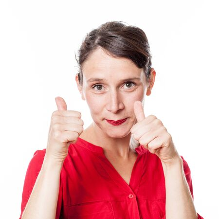two thumbs up: satisfaction concept - closeup of shy 30s woman with two thumbs up approving, congratulating for optimism, white background studio