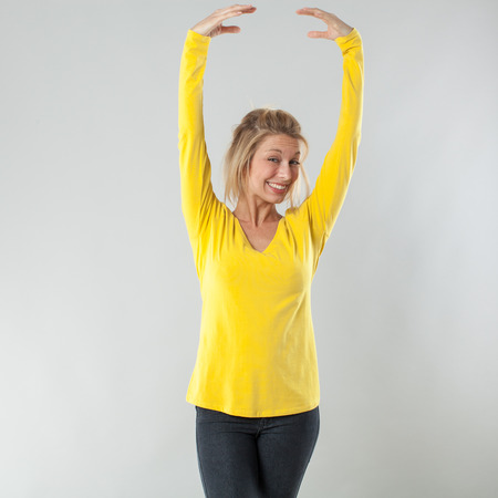 female hand: success concept - smiling 20s blond woman with yellow shirt dancing with graceful hands up for happiness or vitality,studio shot
