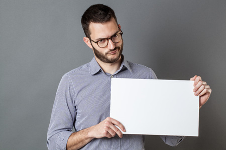 skeptical: panel announcement - skeptical young man with beard and eyeglasses holding a blank banner for copy space text, gray background
