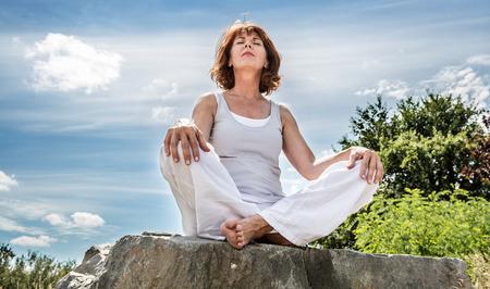 atmung: außerhalb der Ausübung - strahlend 50s Yoga Frau sitzt auf einem Stein, sucht für das seelische Gleichgewicht mit Baum Hintergrund, Untersicht Lizenzfreie Bilder