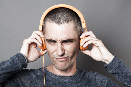 conflicted: painful sound concept - unhappy 30s man frowning in listening to noise or music on orange headphones,dark texture effects,gray background studio