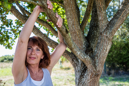 50's: middle aged wellness - happy 50s woman under a tree for metaphor of wellbeing and serenity,summer daylight Stock Photo