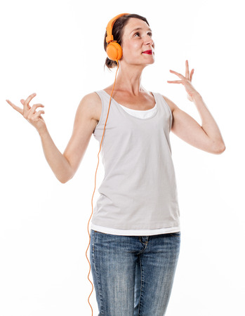 30s: fashionable sound concept - graceful 30s woman smiling in listening to happy music on orange headphones, white background studio Stock Photo