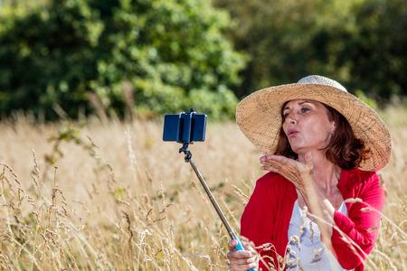 donne mature sexy: all'aperto selfie - sexy donna matura facendo una divertente autoritratto sul telefono cellulare sul bastone in mezzo di erba alta a secco, la luce del giorno d'estate