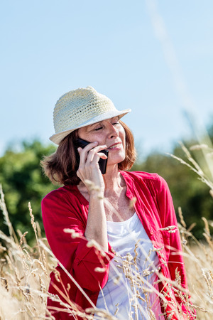 50s: outdoors communication - smiling 50s woman talking on mobile phone in the middle of high dry grass,summer daylight