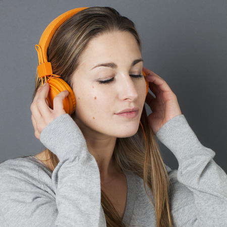 closing eyes: fashionable sound concept - beautiful relaxed young woman closing eyes in listening to cool music on orange headphones, gray background studio