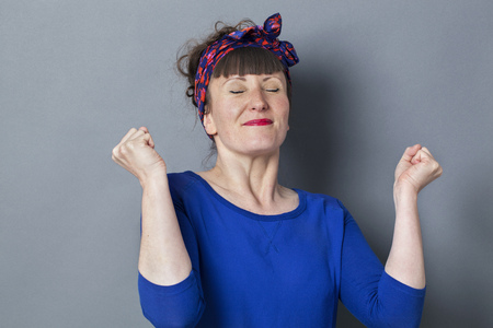 fifties: success concept - happy 30s woman with fifties hairstyle smiling with eyes closed enjoying successful competition,studio shot