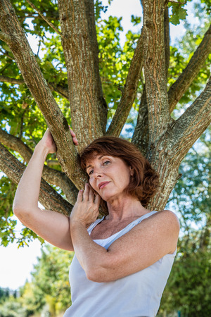 middle aged wellness - serene 50s woman under a tree for metaphor of strength and family roots,summer daylight