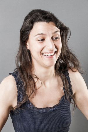 giggling: female natural laughter portrait - happy young woman with natural fine hair giggling or laughing for wellbeing over gray background, studio shot