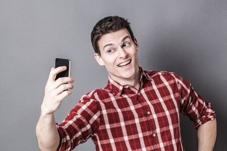 taking photo: male selfie - cheesy young athletic man enjoying taking selfie for seduction over gray background studio, texture effects Stock Photo