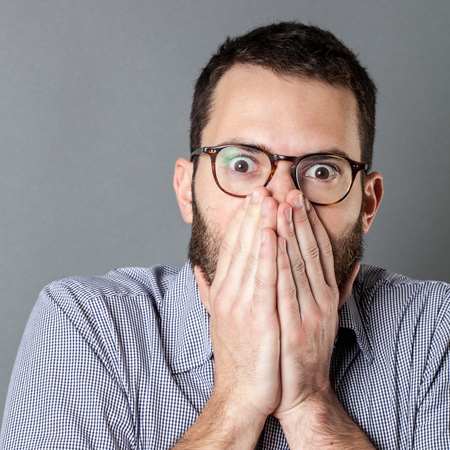 stunned: male mistake concept - stunned young businessman hiding his mouth, eyes wide open, having regret, gray background studio Stock Photo