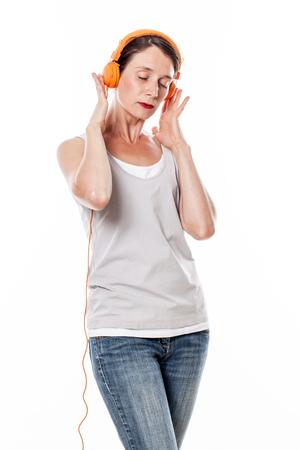 30s: fashionable sound concept - focused 30s female musician enjoying listening to music on orange headphones, white background studio Stock Photo
