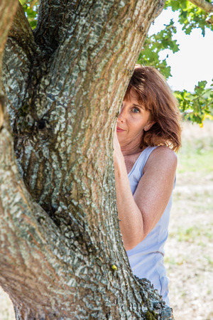 shyness: middle aged wellness - gorgeous mature woman hiding behind a tree for metaphor of shyness and discretion,summer daylight Stock Photo