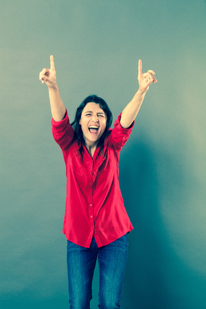 extrovert: success concept - ecstatic 30s woman laughing with extrovert hand gesture to express euphoria or vitality,studio shot, blue effects Stock Photo