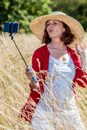 donne mature sexy: all'aperto selfie - sexy donna di mezza et� facendo una divertente autoritratto sul telefono cellulare sul bastone in mezzo di erba alta a secco, la luce del giorno d'estate Archivio Fotografico