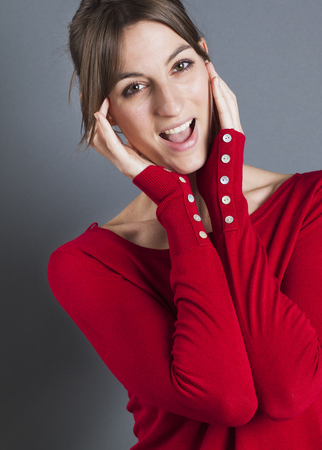 20s  closeup: female model laughter portrait - closeup of thrilled 20s girl laughing, wearing red winter sweater over gray background, studio shot