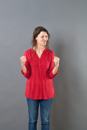 mitigated: struggling concept - pouting 30s woman questioning motivation and challenge with fighting hand gesture for conviction or doubt,studio shot