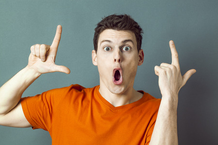 falta de respeto: concepto de la cultura juvenil - joven aturdido con la boca abierta para la muestra de LOL mano para expresar el humor tonto, tiro del estudio, los efectos azules Foto de archivo