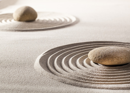 tranquillity: stones or pebbles in the middle of pure waves in sand for concept of tranquillity or wellbeing