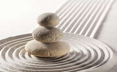 closeup of balanced pebbles in the pure waves in sand for meditation and contemplation Фото со стока
