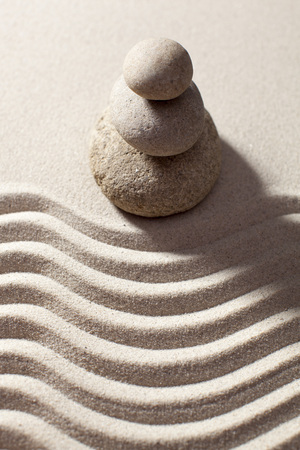 progression: top view of pebbles in balance before waves in sand for progression or spirituality concept