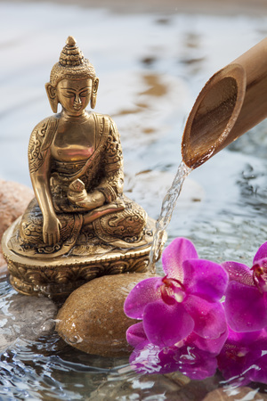 peace pipe: water orchid next to religious symbol with beautiful pebbles, pink orchids and bamboo pipe for source of peace and rejuvenation
