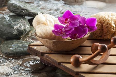 masajes relajacion: accesorios de relajación al lado de agua con esponja vegetal, Kit de masaje y orquídeas rosas para la belleza, la feminidad y la relajación
