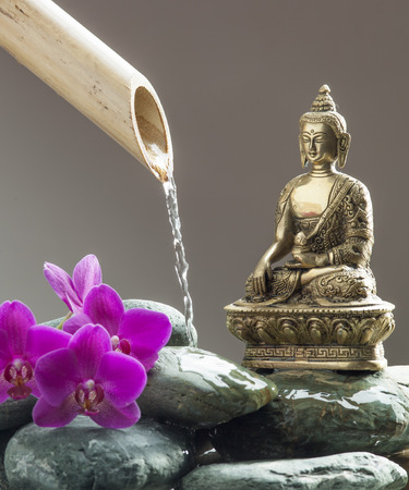 peace pipe: zen Buddha next to symbol of beauty with beautiful pebbles, pink orchids and bamboo pipe for source of peace and meditation