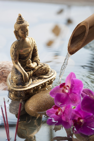 peace pipe: relaxing beauty with meditation symbols with beautiful Buddha in water environment with pebbles, orchids and source of peace and spirituality