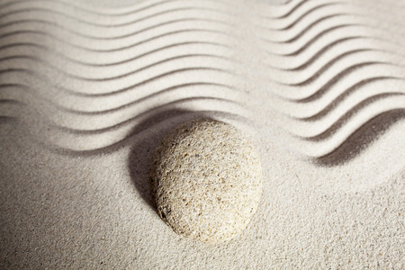 steadiness: top view of sinuous path in zen sand for philosophy of life with one round pebble or stone set on the border waves
